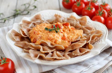 stracchino: Wholegrain Pasta with stracchino cheese and fresh tomatoes close up Stock Photo