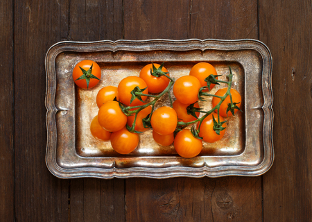 Yellow cherry tomatoes on a metal  tray