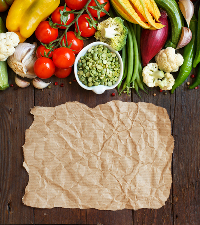craft paper: Green peas in a bowl with fresh vegetables with craft paper  on wood top view Stock Photo