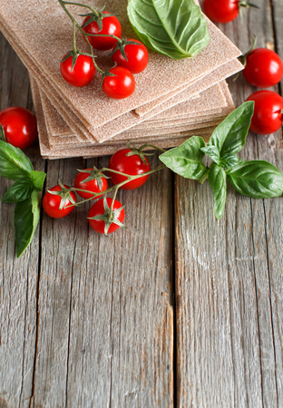 Raw lasagna sheets,basil and cherry tomatoes on a wooden table Stock Photo
