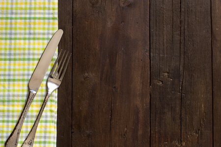 grunge cutlery: Vintage fork and knife on a colorful napkin on wooden table