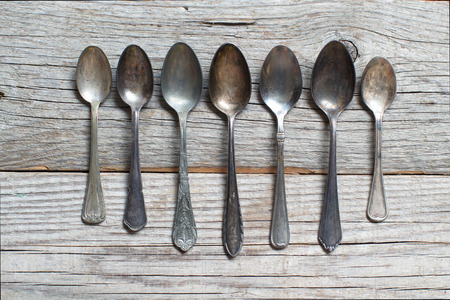 grunge flatware: Vintage spoons with patina on old  wooden table