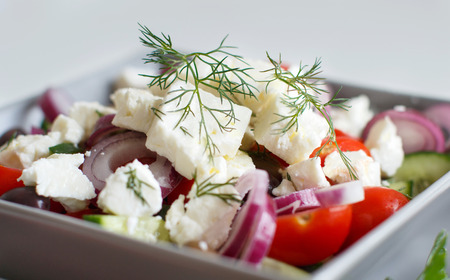 Greek salad with tomatoes, feta cheese, cucumbers, onions and olives