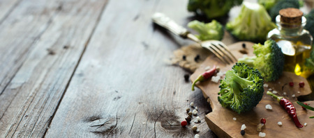 Fresh green broccoli and vegetables on wooden table