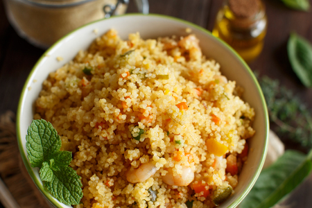 Couscous with shrimps and vegetables in a bowl close up