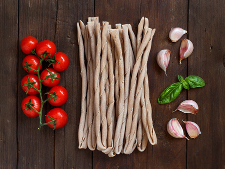 durum: Raw italian  pasta, basil and vegetables on wooden background Stock Photo