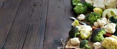 Fresh raw cauliflower and broccoli on an old wooden table top view Archivio Fotografico
