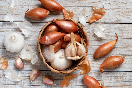 Organic garlic and onion in a basket on wooden table top view Archivio Fotografico
