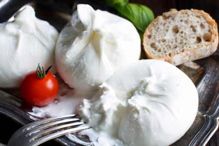 Queso italiano burrata, tomate y albahaca close up Foto de archivo - 71477988