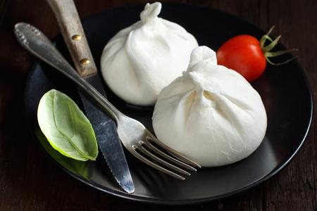 Italian cheese burrata on a plate on a dark background