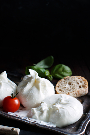 Italian cheese burrata with tomatoe and bread on a dark background
