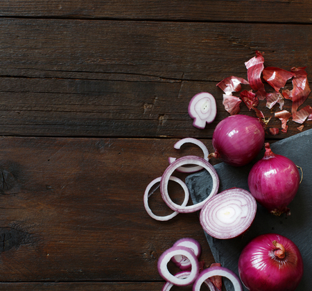 Red onions on a wooden table close up