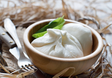 Italian cheese burrata in a bowl with fork and knife