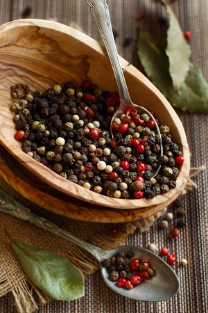 Peppercorn mix in a bowl and bay leaves on a wooden table