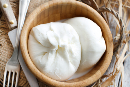 Italian cheese burrata with bread on a wooden background