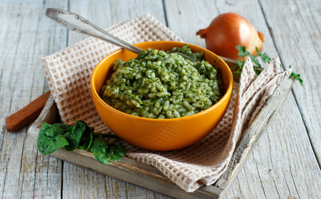 Risotto with spinach cream in a bowl close up