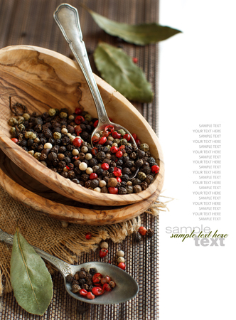 Peppercorn mix in a bowl with a spoon and bay leaves