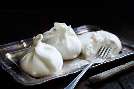 Italian cheese burrata with fork on a dark background