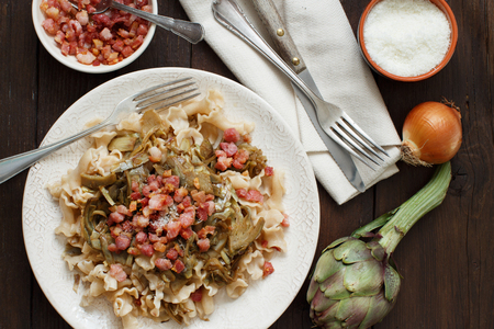 Pasta with artichokes and bacon with ingredients top view