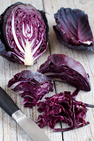 Red cabbage with a knife on a wooden table