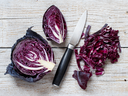 Red cabbage with a knife on a wooden table top view
