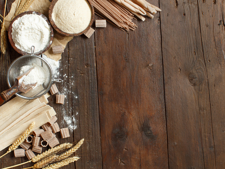 Ingredients and utensils for pasta making on a wooden background