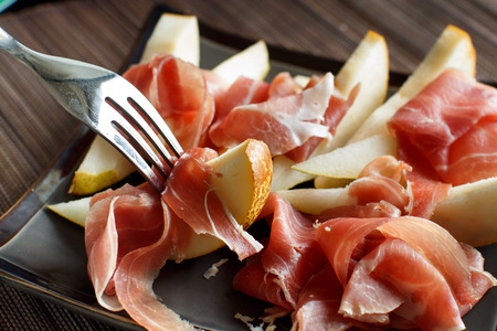 Appetizer with pear and italian parma ham close up