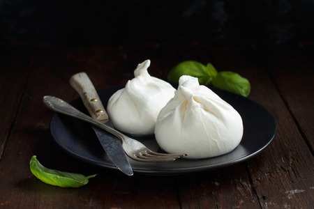 Italian cheese burrata with fork and knife on a dark background Archivio Fotografico