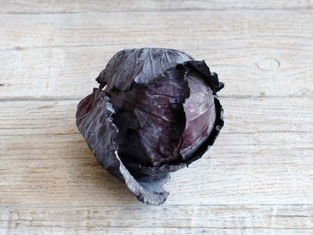 Whole red cabbage on an old wooden table