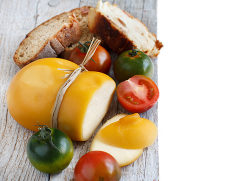 Scamorza, typical italian smoked cheese with homemade bread and tomatoes Stock Photo