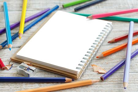 Disegno-pad e matite colorate su un tavolo di legno Archivio Fotografico - 75336107