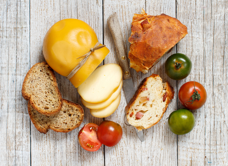Scamorza, pomodoro e pane su una tavola di legno Archivio Fotografico - 75336109
