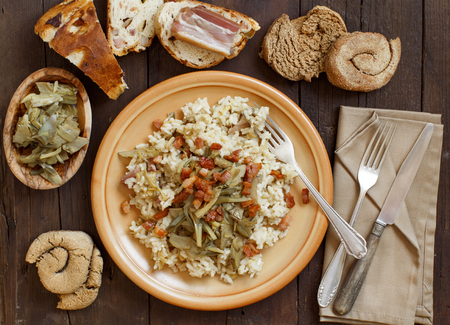 Risotto with artichokes and bacon top view on a wooden table Archivio Fotografico