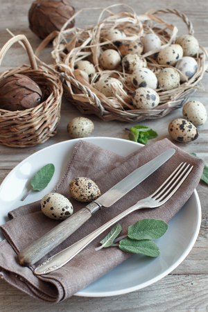 Rustic Easter table setting with eggs and herbs on a wooden table