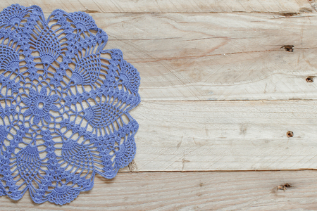 grey pattern: Blue crochet doily on the old wooden  table Stock Photo