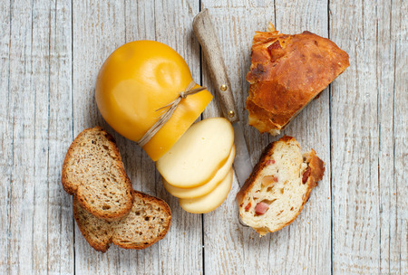 Scamorza, typical italian smoked cheese and homemade bread on wooden table
