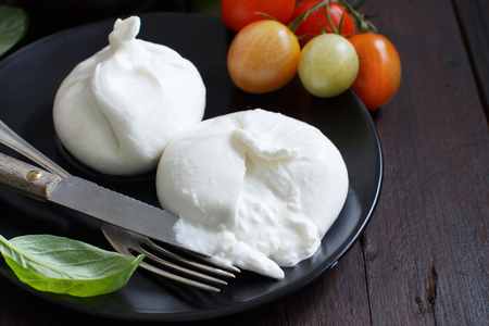 Italian cheese burrata with fork on a dark background Фото со стока - 77906648