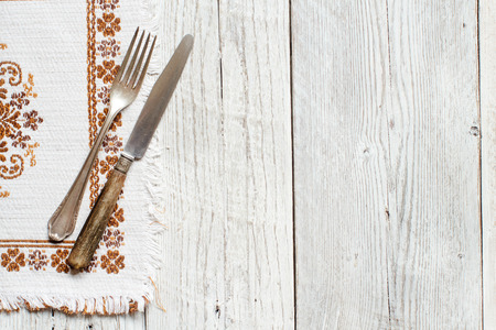 Aged white wood texture background with napkin and fork and knife