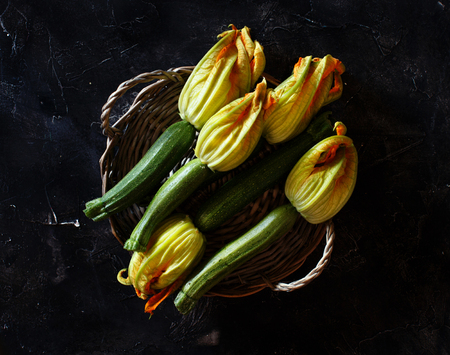Zucchini  with flowers  on a dark background top view Archivio Fotografico