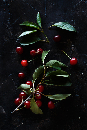 Fresh sour cherries on a dark background top view