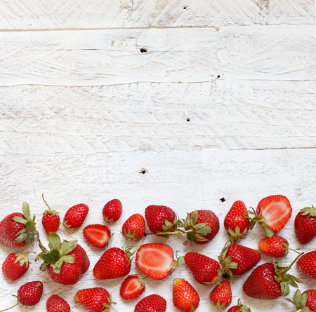 Strawberries on a white  wooden table top view