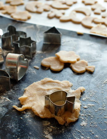 Close up of cookie cutters in a dough on a dark table Archivio Fotografico