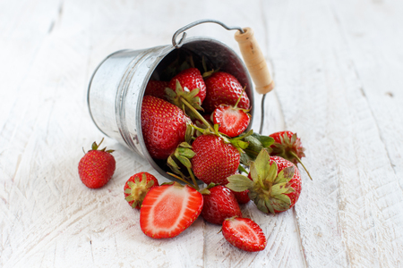 Strawberries in a bucket on a white wooden table