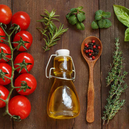 Vegetables, herbs and olive oil on wooden background