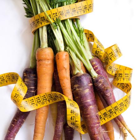 Fresh organic rainbow carrots and yellow measuring type Archivio Fotografico