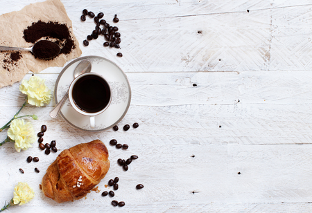 Top view of coffee with croissant on rustic white wood