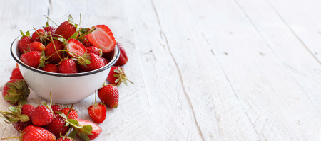 Strawberries in a bowl on a white wooden table