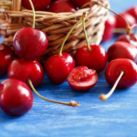 Red cherries in a basket on a blue background