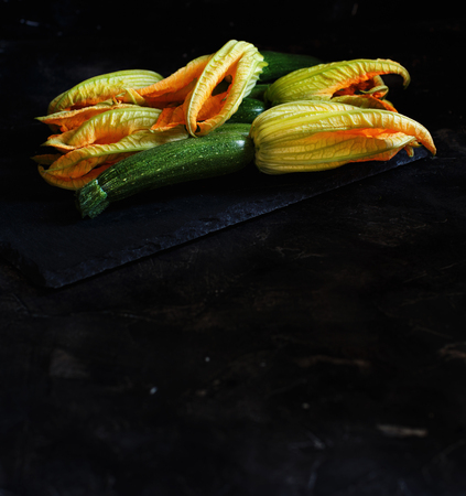 Zucchini  with flowers  on a dark background close up Archivio Fotografico