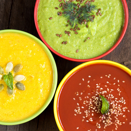Three fresh soups - tomatoes, pumpkin and green peas soups Archivio Fotografico